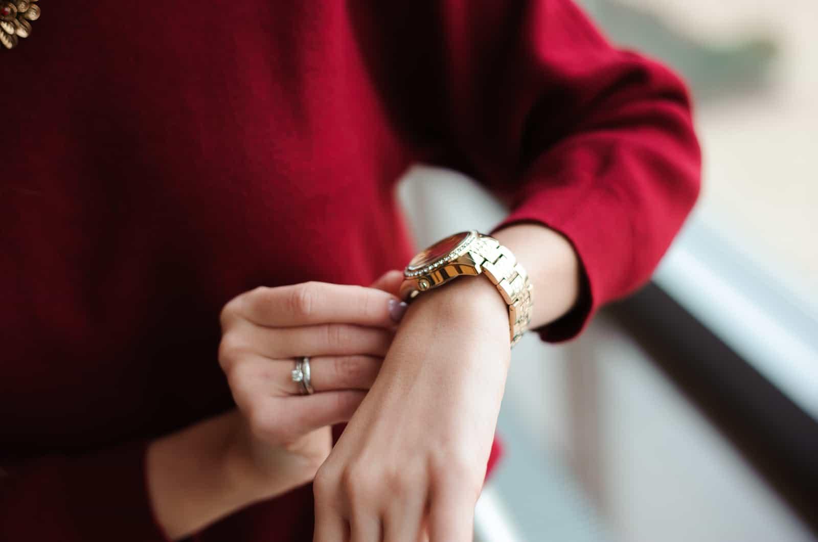 Frau im roten Pullover schaut auf die Uhr