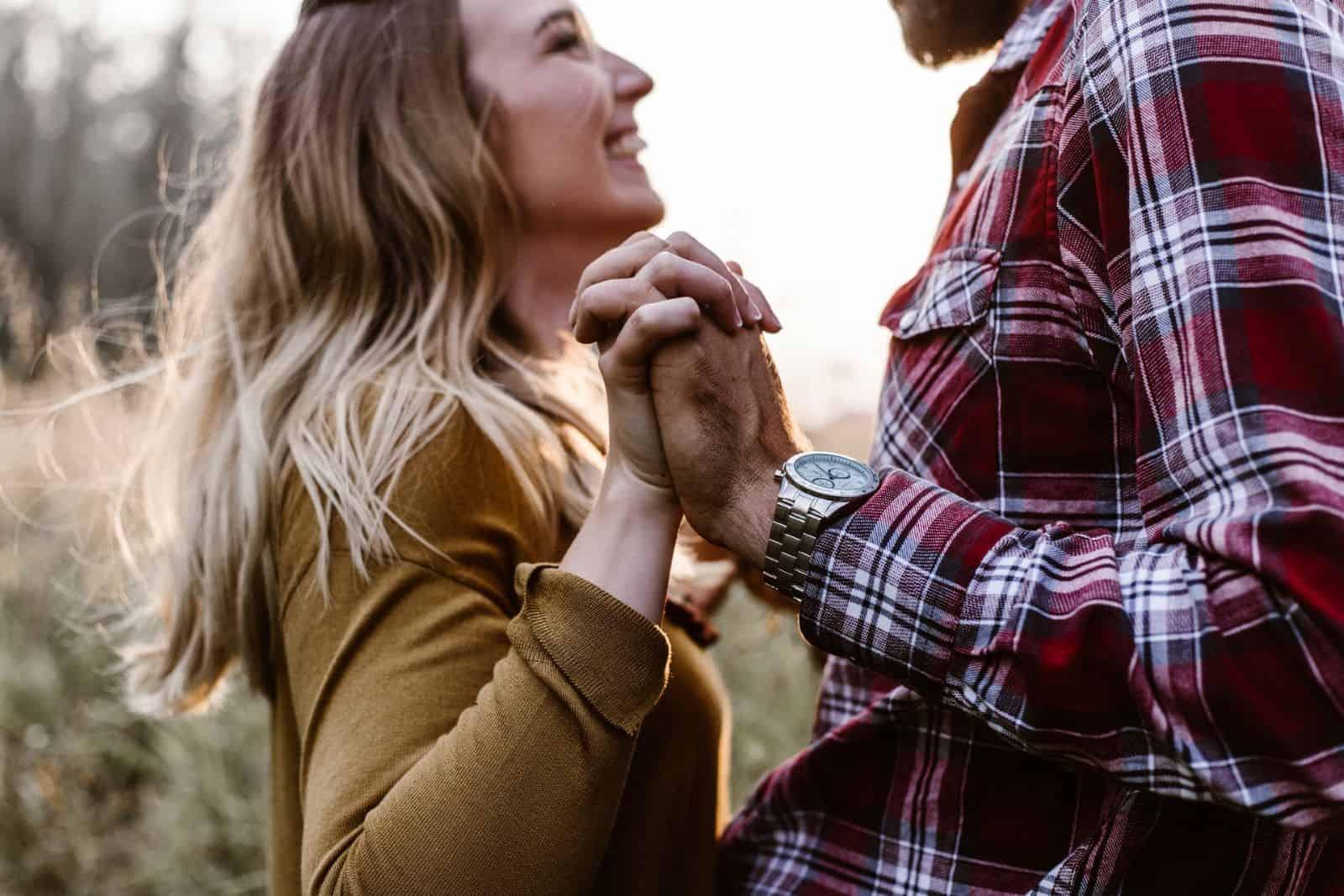 Mann und Frau halten Händchen und lächeln