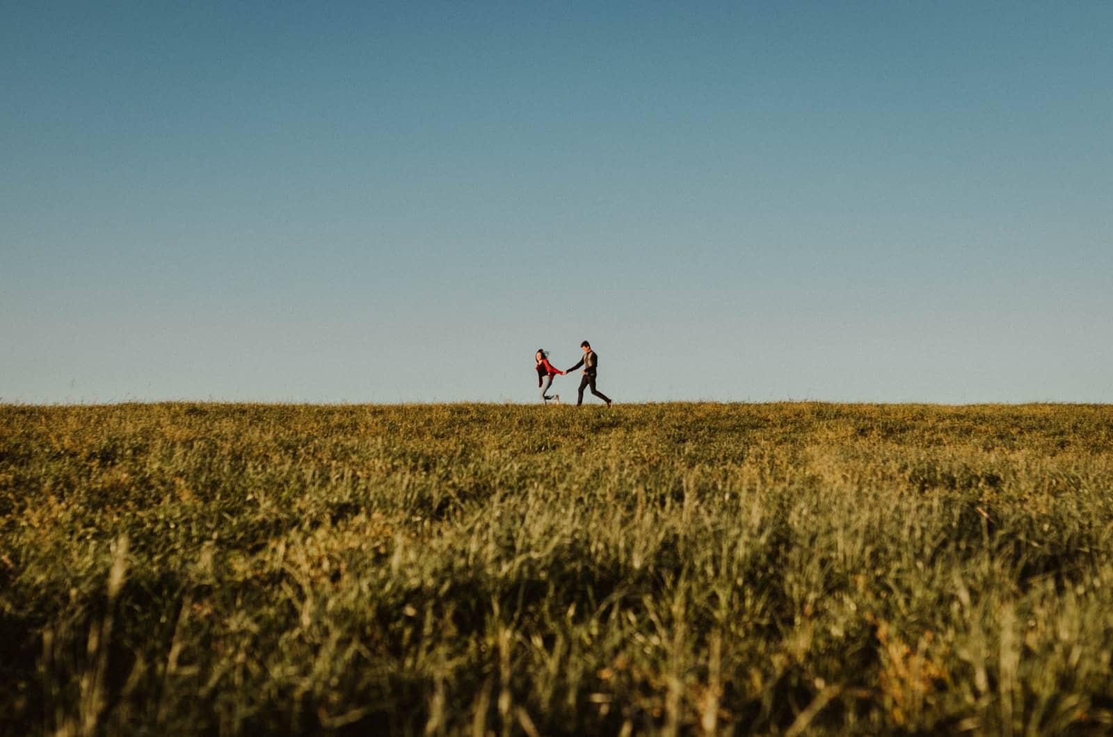 Paar läuft auf einem Feld
