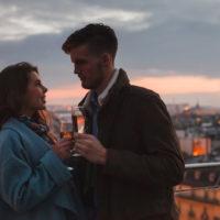 Mann und Frau auf einem Balkon mit Gläsern Champagner