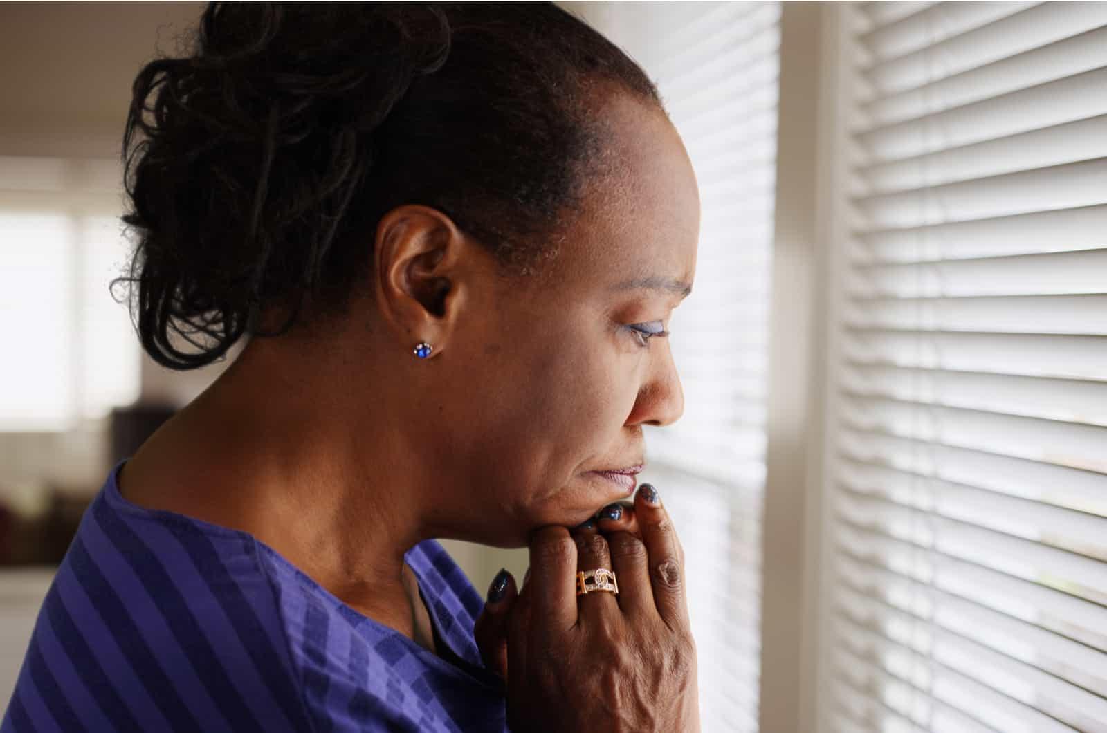 Traurige Frau schaut durch das Fenster