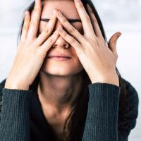 Frau bedeckt ihr Gesicht mit den Händen