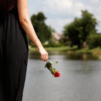 Frau im schwarzen Kleid mit Rose