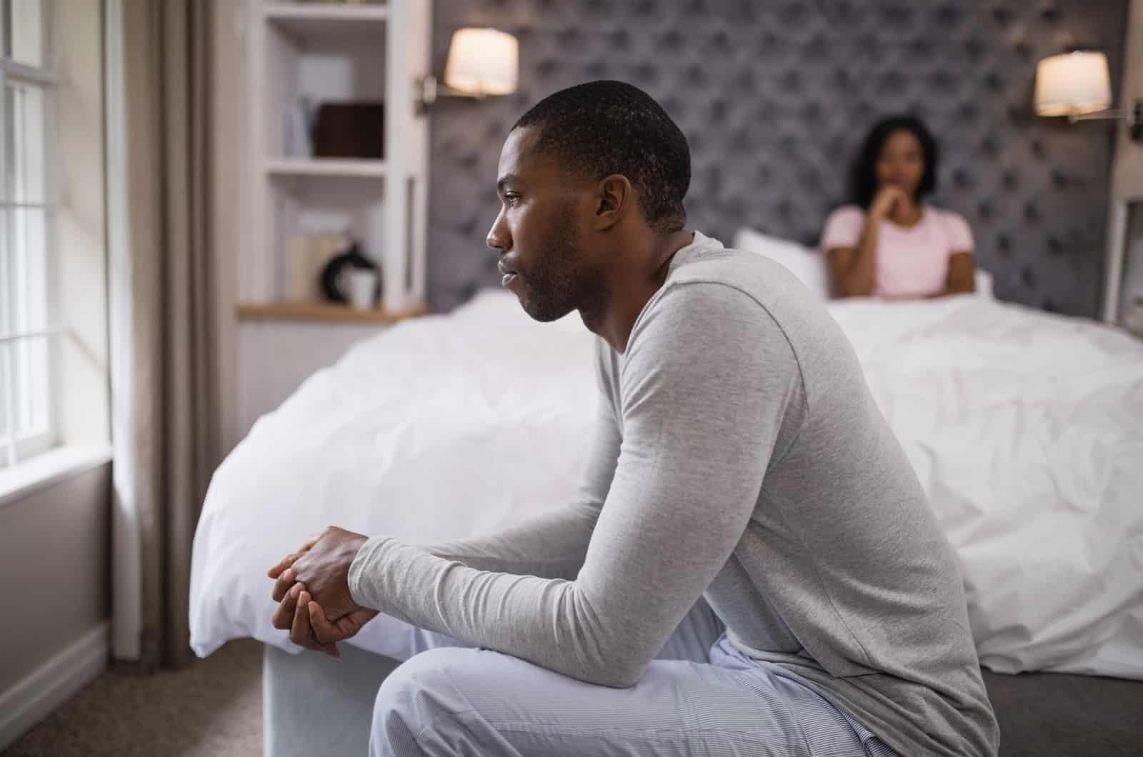 unglücklicher Mann im Schlafzimmer mit Frau im Bett